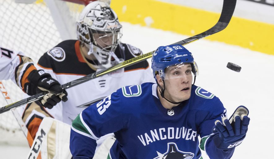 Vancouver Canucks' Bo Horvat catches the puck after Anaheim Ducks goalie John Gibson, back, made a save during the second period of an NHL hockey game Tuesday, March, 27, 2018, in Vancouver, British Columbia. (Darryl Dyck/The Canadian Press via AP)