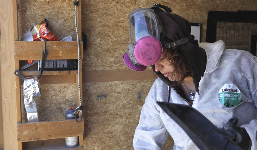Wyoming Weatherization Services employee Lisa Pena sweeps the inside of a trailer on a job site in east Cheyenne, Wyo. The former teen mother and Climb Wyoming graduate has risen through the ranks of the company to become a team leader. (Jacob Byk/The Wyoming Tribune Eagle via AP)
