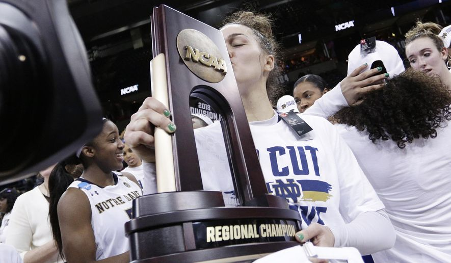 FILe - In this Monday, March 26, 2018, file photo, Notre Dame forward Kathryn Westbeld kisses the tournament trophy after defeating Oregon 84-74 in a regional final at the NCAA women's college basketball tournament, in Spokane, Wash. About five hours after returning to Notre Dame after winning the Spokane Regional , Kathryn Westbeld limped Tuesday into her business class at Notre Dame _ quantitative decision modeling. No one would have blamed the 6-foot-2 senior forward if she had made her way to the back of the room to find a seat and get more sleep.(AP Photo/Young Kwak, File)