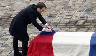 French President Emmanuel Macron posthumously awards the Legion of Honor to Lt. Col. Arnaud Beltrame during a ceremony Wednesday, March 28, 2018, at the Hotel des Invalides in Paris. (AP Photo/Christophe Ena)
