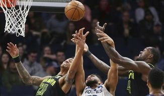 Minnesota Timberwolves forward Karl-Anthony Towns (32) vies for a rebound with Atlanta Hawks forwards Dewayne Dedmon (14) and John Collins (20) during the first quarter of an NBA basketball game Wednesday, March 28, 2018, in Minneapolis. (AP Photo/Andy Clayton-King)