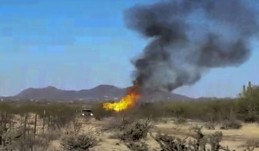 "This still image taken from video provided by Rob Hammersmark shows a fire from a hot air balloon that crashed in the desert outside Phoenix, Ariz. on Wednesday, March 28, 2018. Authorities say the hot air balloon carrying 13 people crashed and caught fire next to a dirt road in the desert igniting a small brush fire but causing no injuries. It's not immediately known what caused the Wednesday morning crash. Phoenix fire Capt. Jake Van Hook says it started ""only a small amount of fire,"" which crews quickly extinguished. (Rob Hammersmark via AP)"