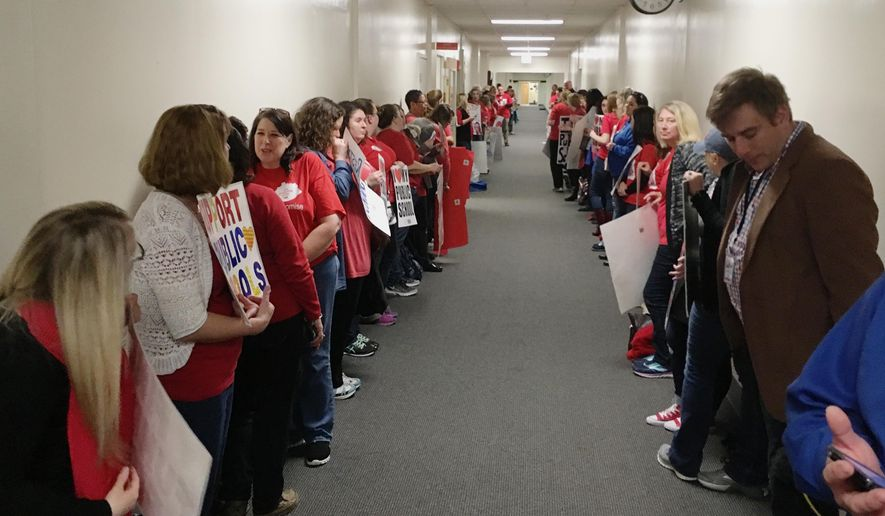 Public school teachers line the hallway outside of a room in the Kentucky Capitol annex in Frankfort, Ky., where budget negotiators were scheduled to meet, Wednesday, March 28, 2018. Negotiations over Kentucky's two-year operating budget appear to be slow-going as lawmakers have not officially met to discuss the spending plan. (AP Photo/Adam Beam)