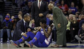 Philadelphia 76ers' Joel Embiid, center, lies not he court after an injury during the first half of an NBA basketball game against the New York Knicks, Wednesday, March 28, 2018, in Philadelphia. (AP Photo/Matt Slocum)
