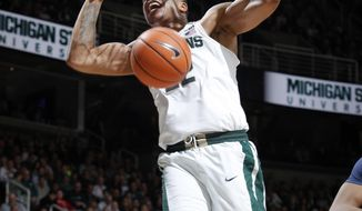 FILE - In this Jan. 31, 2018, file photo, Michigan State's Miles Bridges dunks as Penn State's Lamar Stevens (11) and Michigan State's Nick Ward, left, watch during the first half of an NCAA college basketball game, in East Lansing, Mich. Michigan State star Miles Bridges is skipping his final two seasons of eligibility and entering the NBA draft. The school announced Bridges' departure Wednesday, March 28, 2018. (AP Photo/Al Goldis, File)