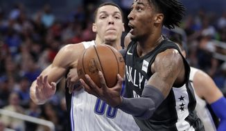 Brooklyn Nets' Rondae Hollis-Jefferson, right, looks for a shot in front of Orlando Magic's Aaron Gordon (00) during the second half of an NBA basketball game, Wednesday, March 28, 2018, in Orlando, Fla. (AP Photo/John Raoux)