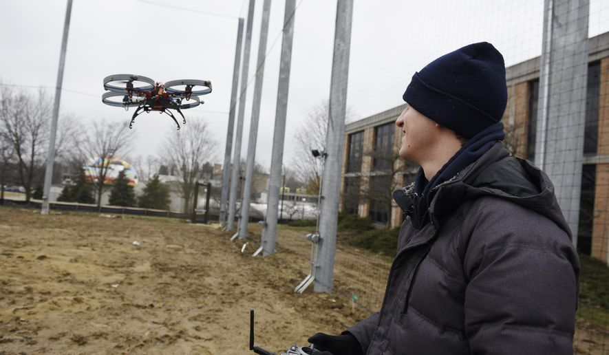 Matthew Romano, 1st year PhD Robotics student flies his drone inside the new M-Air netted autonomous aerial vehicle outdoor lab at the University of Michigan on Wednesday, March 28, 2018, in Ann Arbor, Mich. The facility can test drones in just about any kind of weather.  (Clarence Tabb Jr./Detroit News via AP)
