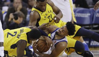 Golden State Warriors' Quinn Cook, bottom, right, scramble for a loose ball against Indiana Pacers' Darren Collison (2) and Thaddeus Young (21) during the first half of an NBA basketball game Tuesday, March 27, 2018, in Oakland, Calif. (AP Photo/Marcio Jose Sanchez)