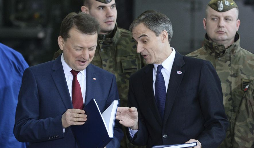 Polish Defense Minister Mariusz Blaszczak, left, and U.S. ambassador to Poland Paul Jones check the just signed deal to buy the U.S. made air defense Patriot system in Warsaw, Poland, Wednesday, March 28, 2018. Poland has signed a $4.75 billion deal with the United States to buy the Patriot missile systems as it seeks to bolster its defenses against a resurgent Russia. (AP Photo/Alik Keplicz)
