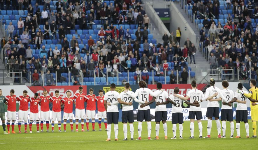 France's and Russian players observe a minute of silence in memory of the victims of a fire in a multi-story shopping center in the Russian city of Kemerovo during the international friendly soccer match between Russia and France at the Saint Petersburg stadium in St.Petersburg, Russia, Tuesday, March 27, 2018. (AP Photo/Dmitri Lovetsky)