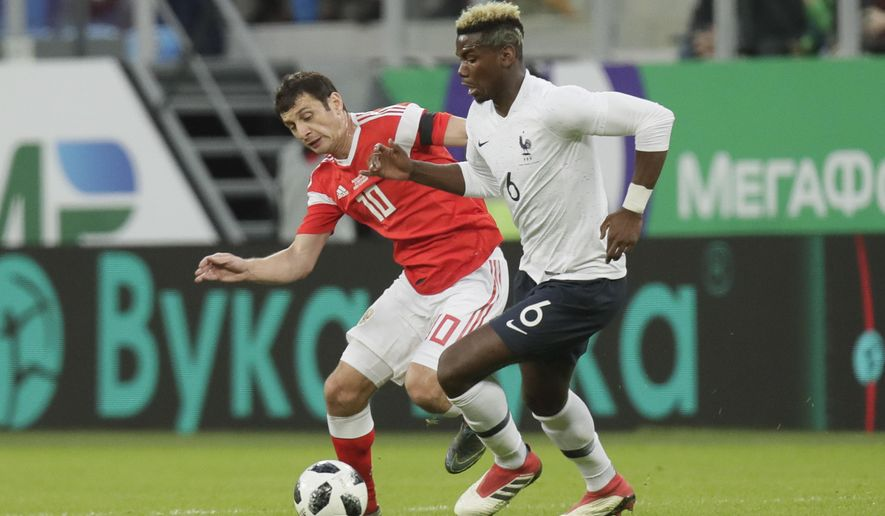 France's Paul Pogba, right, duels for the ball with Russia's Fyodor Smolov during the international friendly soccer match between Russia and France at the Saint Petersburg stadium in St.Petersburg, Russia, Tuesday, March 27, 2018. (AP Photo/Dmitri Lovetsky)