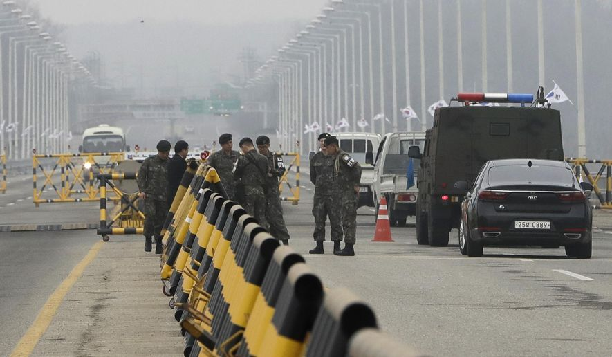 South Korean soldiers wait for vehicles carrying a South Korean delegation at Unification Bridge, which leads to the Panmunjom in the Demilitarized Zone in Paju, South Korea, Thursday, March 29, 2018. The delegation led by Unification Minister Cho Myoung-gyon will hold a high-level talks with North Korea at the northern side of the Panmunjom. (AP Photo/Lee Jin-man)