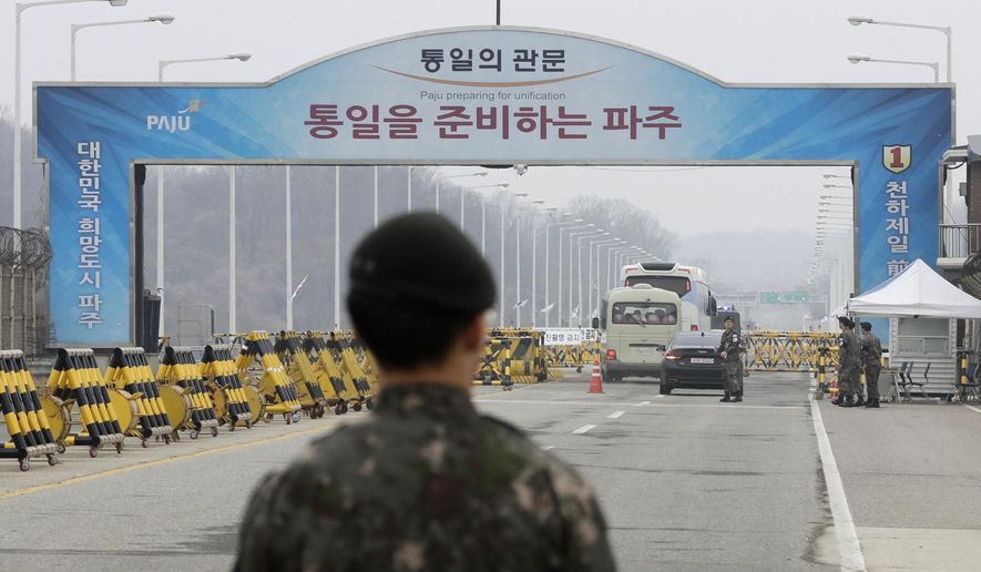 South Korean soldiers stand as vehicles carrying a South Korean delegation pass the Unification Bridge, which leads to the Panmunjom in the Demilitarized Zone in Paju, South Korea, Thursday, March 29, 2018. The delegation led by Unification Minister Cho Myoung-gyon will hold a high-level talks with North Korea at the northern side of the Panmunjom. (AP Photo/Lee Jin-man)