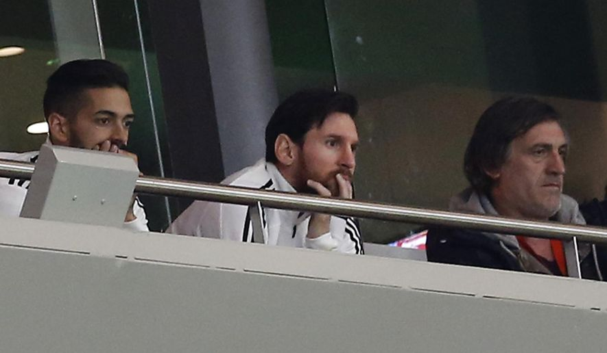 Argentina's Lionel Messi, center, watches from the tribune during the international friendly soccer match between Spain and Argentina at the Wanda Metropolitano stadium in Madrid, Spain, Tuesday March 27, 2018. (AP Photo/Paul White)