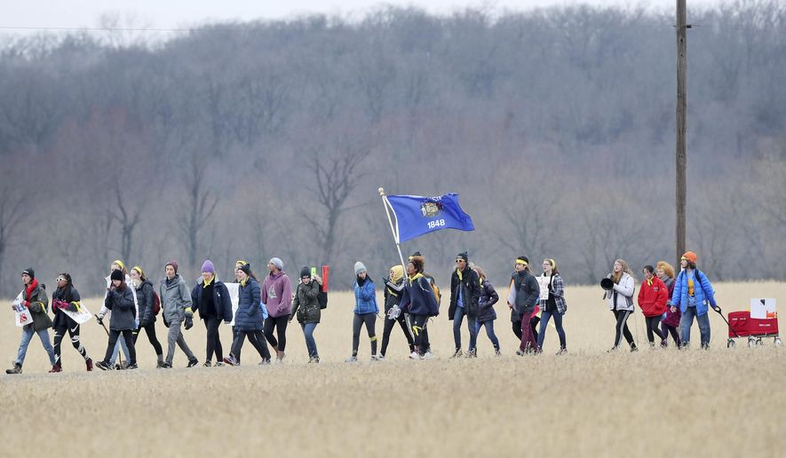 A group of about 40 students make their way along Old Highway 92 south of Evansville, Wis., on Tuesday, March 27, 2018,  as they march to U.S. Rep. Paul Ryan's hometown of Janesville to call for stricter gun control laws. An end-of-march event is scheduled at Traxler Park in Janesville on Wednesday, March 28 at noon. (Anthony Wahl/The Janesville Gazette via AP)