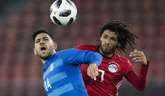 Greece's Anastasios Bakasetas, left, fights for the ball against Egypt's Mohamed Elneny, during the friendly soccer game Egypt against Greece at the Letzigrund stadium in Zurich, Switzerland, Tuesday, March 27, 2018. (Ennio Leanza/Keystone via AP)