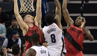 Memphis Grizzlies guard MarShon Brooks (8) shoots between Portland Trail Blazers center Zach Collins, left, and forward Al-Farouq Aminu (8) in the second half of an NBA basketball game Wednesday, March 28, 2018, in Memphis, Tenn. (AP Photo/Brandon Dill)
