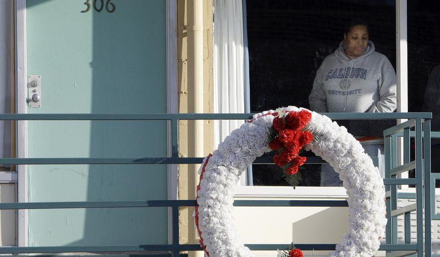 FILE - In Jan. 19, 2009, file photo, a woman looks out of a window while visiting the National Civil Rights Museum located at the Lorraine Motel in Memphis, Tenn., on the nationwide holiday honoring Martin Luther King Jr. The wreath marks the location where King was killed while standing on the balcony April 4, 1968. Travelers will find a variety of events and sites in Memphis and elsewhere honoring King's legacy on the 50th anniversary of his death.(AP Photo/Mark Humphrey, File)