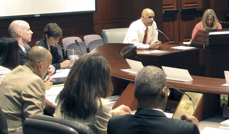 Connecticut state Rep. Angel Arce, second from right rear, testifies before a state crime records task force Wednesday, Sept. 18, 2013, in Hartford, Conn. Arces' father died after a hit-and-run accident in 2008 that was caught on surveillance video. Arce said he was upset that videos of the accident are all over the Internet and urged the panel to consider victims' privacy when deciding when to release records. The Task Force on Victim Privacy and the Public's Right to Know was set up in response to public records requests related to the Newtown school shootings that killed 20 first-graders and six adults in December. (AP Photo/Dave Collins)