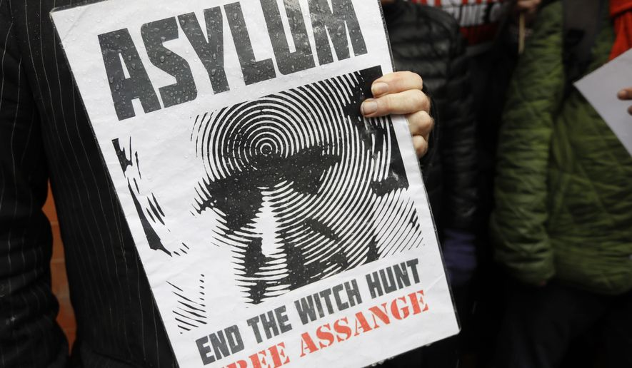 A supporter of Julian Assange holds a banner during a demonstration outside the Ecuadorian Embassy in London, Thursday, March 29, 2018. (AP Photo/Kirsty Wigglesworth)