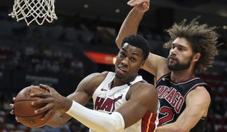 Miami Heat center Hassan Whiteside, left, grabs a defensive rebound in front of Chicago Bulls center Robin Lopez, right, during the first half of an NBA basketball game Thursday, March 29, 2018, in Miami. (AP Photo/Joel Auerbach)