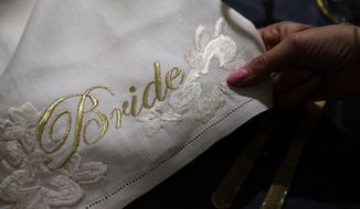 In this photo taken on Wednesday March 28, 2018, a detail of a napkin with the word 'Bride' embroidered in gold on display at the Wedding Gallery, in London. The big decisions have been made: the venue, the guest list, the menu and the flowers. Now, with 50 days to go until the wedding of Prince Harry and Meghan Markle, it's time for the details that will make a large royal wedding feel personal and intimate. That's the view of Anna McGregor, director of the Wedding Gallery, one of Britain's leading wedding planning agencies. (AP Photo/Alastair Grant)