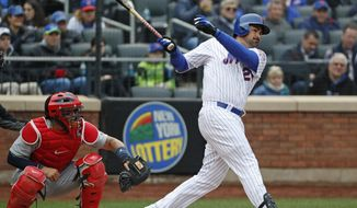 New York Mets' Adrian Gonzalez hits a fifth-inning RBI double in an opening day baseball game against the St. Louis Cardinals, Thursday, March 29, 2018, in New York. Cardinals catcher Yadier Molina is behind the plate. (AP Photo/Kathy Willens)