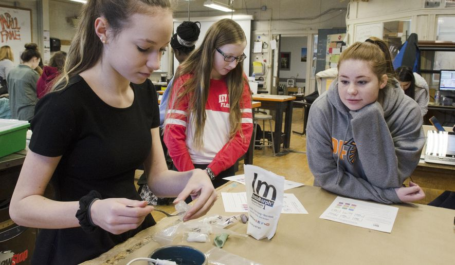 In a March 19, 2018 photo, 9th graders Angela Alexy, Zoe Doyle, and Sarah Retallick use Instamorph to mold a custom phone cord holder at Pennsbury High School in Falls Township, Pa. Bucks County schools are involving girls in STEM programs. [David Garrett/Bucks County Courier Times via AP)