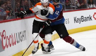 Philadelphia Flyers center Claude Giroux, left, struggles to break away from Colorado Avalanche defenseman Patrik Nemeth during the second period of an NHL hockey game Wednesday, March 28, 2018, in Denver. (AP Photo/David Zalubowski)