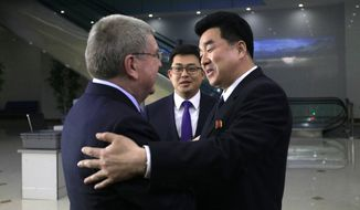 International Olympic Committee (IOC) President Thomas Bach, left, is greeted by North Korean Sports Minister Kim Il Guk on his arrival at the Pyongyang Airport in North Korea, Thursday, March 29, 2018. IOC President Bach arrived in North Korea on Thursday after playing a key role in allowing it to participate in last month's Pyeongchang Olympic Games in South Korea. (AP Photo/Jon Chol Jin)