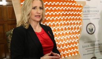 In front of a backdrop that included 401 pill bottles affixed to a wooden map of Arkansas, state Attorney General Leslie Rutledge discusses her lawsuit against three drug manufacturers that she says have contributed to an opioid crisis in the state. ed for 401 deaths two years ago. Rutledge, who appeared with Gov. Asa Hutchinson at a state Capitol news conference on Thursday, March 29, 2018, said drug abuse caused 401 deaths in 2016. (AP Photo/Kelly P. Kissel)