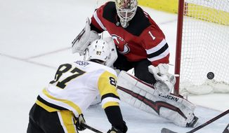 A shot by Pittsburgh Penguins center Sidney Crosby (87) enters the net behind New Jersey Devils goaltender Keith Kinkaid (1) for a goal during overtime of an NHL hockey game, Thursday, March 29, 2018, in Newark, N.J. The Penguins won 4-3. (AP Photo/Julio Cortez)