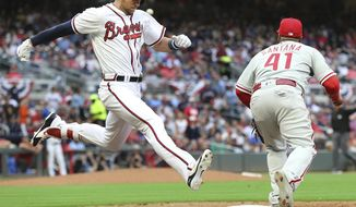 Atlanta Braves' Lane Adams beats the throw to Philadelphia Phillies first baseman Carlos Santana for a single during the seventh inning of a baseball game Thursday, March 29, 2018, in Atlanta. (Curtis Compton/Atlanta Journal-Constitution via AP)