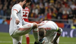 Spain's Sergio Ramos, right, kisses the shoe of Spain's Isco Alarcon, left, after scoring during the international friendly soccer match between Spain and Argentina at the Wanda Metropolitano stadium in Madrid, Spain, Tuesday March 27, 2018. Spain defeated Argentina with 6-1, Isco scored three goals. (AP Photo/Paul White)