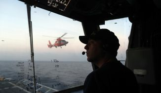 FILE - In this March 2, 2017 photo, an unidentified U.S. Coast Guardsman communicates with the pilot of a helicopter during take-off and landing exercises on the U.S. Coast Guard cutter Stratton in the eastern Pacific Ocean. The U.S. Coast Guard is teaming up with the Mexican and Colombian navies off South America's Pacific coast to go after seafaring smugglers, opening a new front in the drug war. (AP Photo/Dario Lopez-Mills, File)