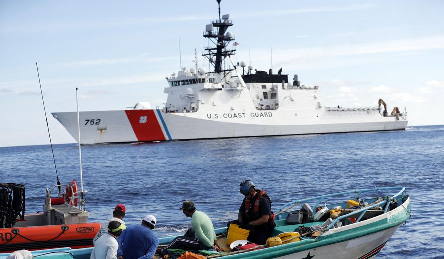 In this Feb. 23, 2017, file photo, a U.S. Coast Guard law enforcement team from the USCG cutter Stratton boards a small fishing boat that was stopped carrying close to 700 kilos of pure cocaine, in the Pacific Ocean hundreds of miles south of the Guatemala-El Salvador border. (AP Photo/Dario Lopez-Mills, File)