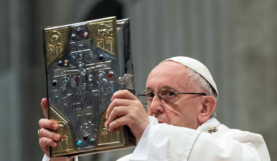 Pope Francis holds up the Gospel as he celebrates a Chrism Mass inside St. Peter's Basilica, at the Vatican, Thursday, March 29, 2018. Francis urged priests on Thursday to be spiritually close to their flocks and not insist on preaching only laws when they sin. (Vatican Media via AP)