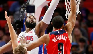 Detroit Pistons center Andre Drummond defends against a shot by Washington Wizards guard Ramon Sessions (9) as Detroit guard Luke Kennard (5) helps defend on the play during the first half of an NBA basketball game Thursday, March 29, 2018, in Detroit. (AP Photo/Duane Burleson)