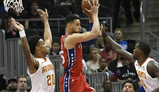 Philadelphia 76ers guard Ben Simmons, center, looks to pass as Atlanta Hawks forward John Collins, left, and center Dewayne Dedmon, right, defend during the first half of an NBA basketball game Friday, March 30, 2018, in Atlanta. (AP Photo/John Amis)