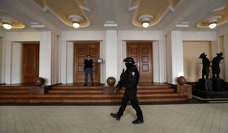 In this Friday, Nov. 24, 2017, file photo, a prison guard walks outside a courtroom during an appeal by Yevgeniy Nikulin from Russia who faces charges of hacking computers of American companies, in Prague, Czech Republic. The Czech Republic extradited a Russian man to the U.S. to face charges of hacking computers at LinkedIn, Dropbox and other American companies, an official said Friday, March 30, 2018. Nikulin was flown to the U.S. overnight, Justice Ministry spokeswoman Tereza Schejbalova said. (AP Photo/Petr David Josek)