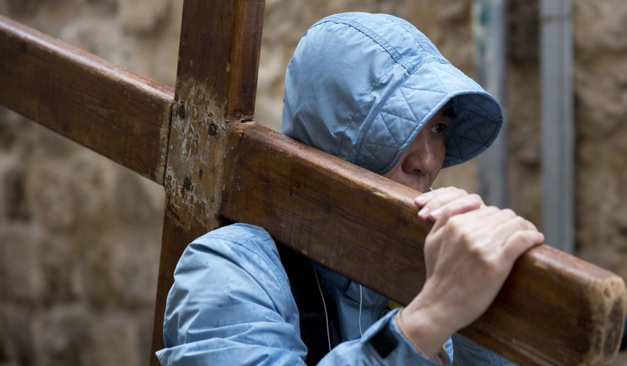 A Christian worshipper holds a cross as he walks along the Via Dolorosa toward the Church of the Holy Sepulchre, traditionally believed by many to be the site of the crucifixion of Jesus Christ, during the Good Friday procession in Jerusalem's Old City. (AP Photo/Ariel Schalit) ** FILE **