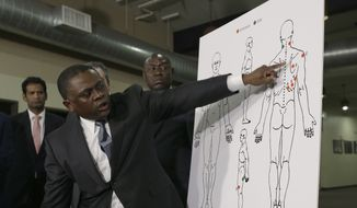 Pathologist, Dr. Bennet Omalu, gestures to a diagram showing the gun shot wounds he found on the body of police shooting victim Stephon Clark, during a news conference Friday, March 30, 2018, in Sacramento, Calif. Omalu was hired for Clark's family to conduct an independent autopsy. (AP Photo/Rich Pedroncelli)