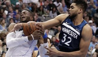 Dallas Mavericks center Nerlens Noel, left, and Minnesota Timberwolves center Karl-Anthony Towns (32) wrestle for control of a rebound in the second half of NBA basketball game in Dallas, Friday, March 30, 2018. (AP Photo/Tony Gutierrez)