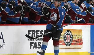 Colorado Avalanche defenseman Tyson Barrie, front, is congratulated as he passes the team box after scoring a power-play goal against the Chicago Blackhawks in the second period of an NHL hockey game Friday, March 30, 2018, in Denver. (AP Photo/David Zalubowski)