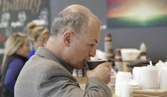 Afshin Afshar takes a sip from a coffee drink he bought at a Philz Coffee shop in San Francisco, Friday, March 30, 2018. Coffee sellers will have to post ominous warnings in California because each cup contains a chemical linked to cancer, a judge ruled. The culprit is a byproduct of the bean roasting process that is a known carcinogen and has been at the heart of an eight-year legal struggle between a tiny nonprofit group and Big Coffee companies. (AP Photo/Jeff Chiu) ** FILE **