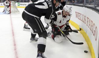 Los Angeles Kings center Jeff Carter (77) and teammate Anze Kopitar, rear, and Arizona Coyotes defenseman Oliver Ekman-Larsson (23) battle in the corner during the second period of an NHL hockey game in Los Angeles Thursday, March 29, 2018. (AP Photo/Reed Saxon)