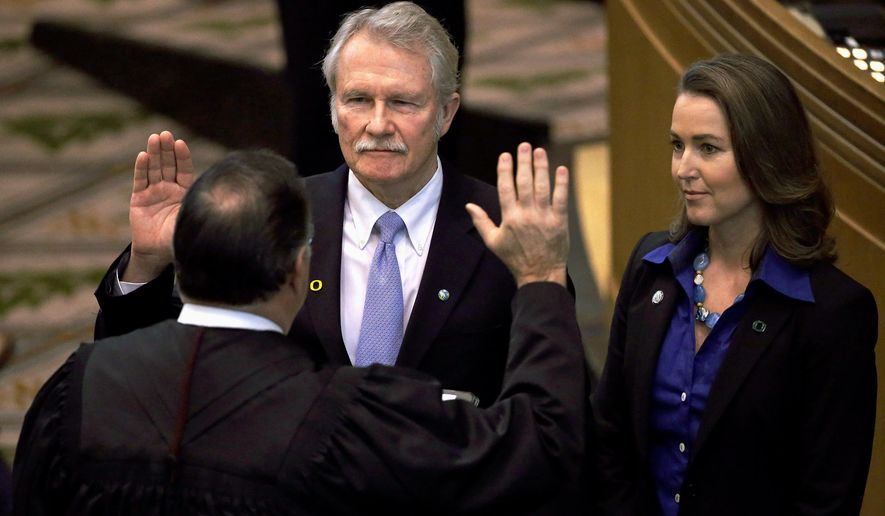 FILE - In this Jan. 12, 2015, file photo, Oregon Gov. John Kitzhaber, left, is joined by his fiancee, Cylvia Hayes, as he is sworn in for an unprecedented fourth term in Salem, Ore. The Oregon Government Ethics Commission has voted to accept a settlement with former Gov. Kitzhaber that requires him to pay a $20,000 fine for violating state ethics laws. Kitzhaber attended a meeting Friday, March 30, 2018, in Salem and expressed regret for his mistakes, The Statesman Journal reported. (AP Photo/Don Ryan, File)