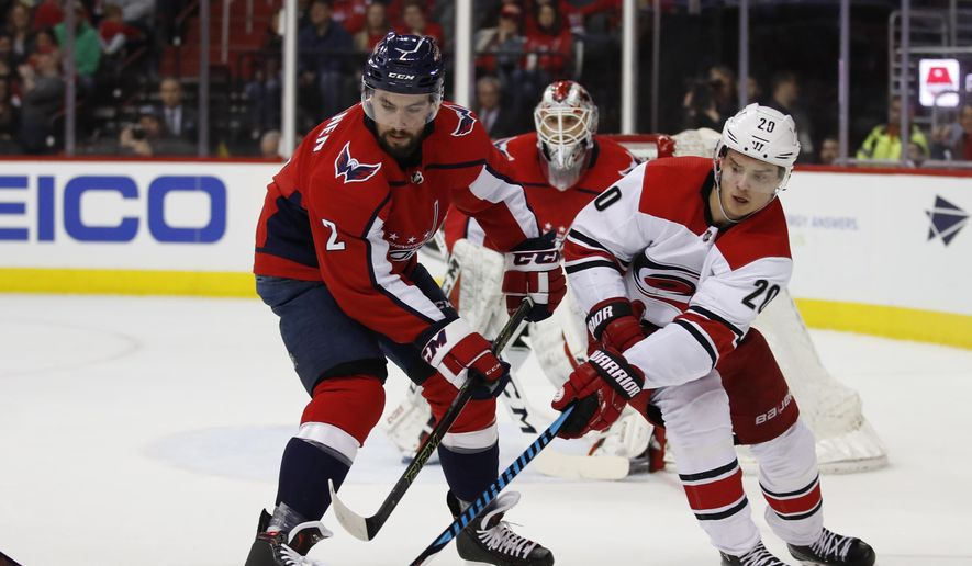 Washington Capitals defenseman Matt Niskanen (2) and Carolina Hurricanes right wing Sebastian Aho (20) battle for control of the puck during the first period of an NHL hockey in Washington, Friday, March 30, 2018. (AP Photo/Carolyn Kaster)