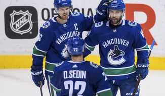Vancouver Canucks center Henrik Sedin (33), of Sweden; center Sam Gagner (89); and left wing Daniel Sedin (22), of Sweden, celebrate Gagner's goal against the Edmonton Oilers during the second period of an NHL hockey game Thursday, March 29, 2018, in Vancouver, British Columbia. (Darryl Dyck/The Canadian Press via AP)