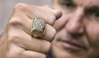 In this Monday, March 26, 2018 photo, former Super Bowl MVP Mark Rypien displays his Super Bowl ring in Spokane, Wash. Rypien said he has attempted suicide, hired prostitutes and suffers from persistent depression, and wonders if he suffered brain injuries while playing football. (Dan Pelle /The Spokesman-Review via AP)